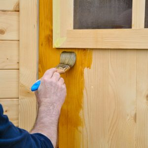 Aquadecks being applied to a chalet door - ©Adfields