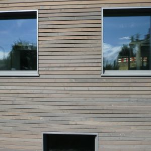 Grey Aquadecks applied to cladding on a commercial building
