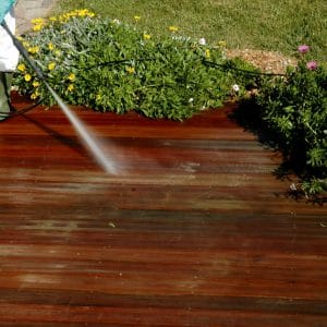 Pressure washer being used on a garden deck
