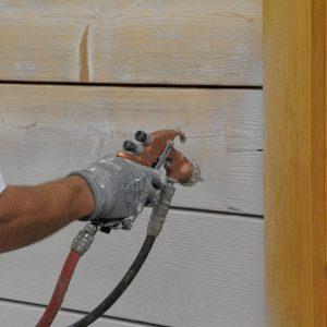 SCS being applied to house cladding via air spray - ©Adfields