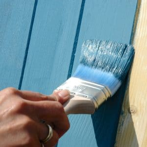 Blue SCS being applied to cladding with a brush