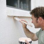 Man applying E-B to the external wall of a house