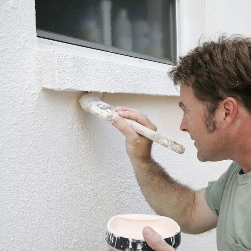 Man applying E-B to the external wall of a house