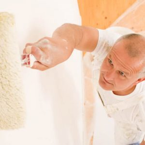 Decorating Supplies - mature man painting white wall with paint roller
