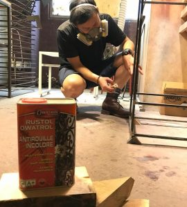 Man using Owatrol Oil to finish metal legs on furniture