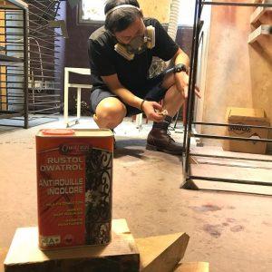 Man using Owatrol Oil to finish metal legs on furniture