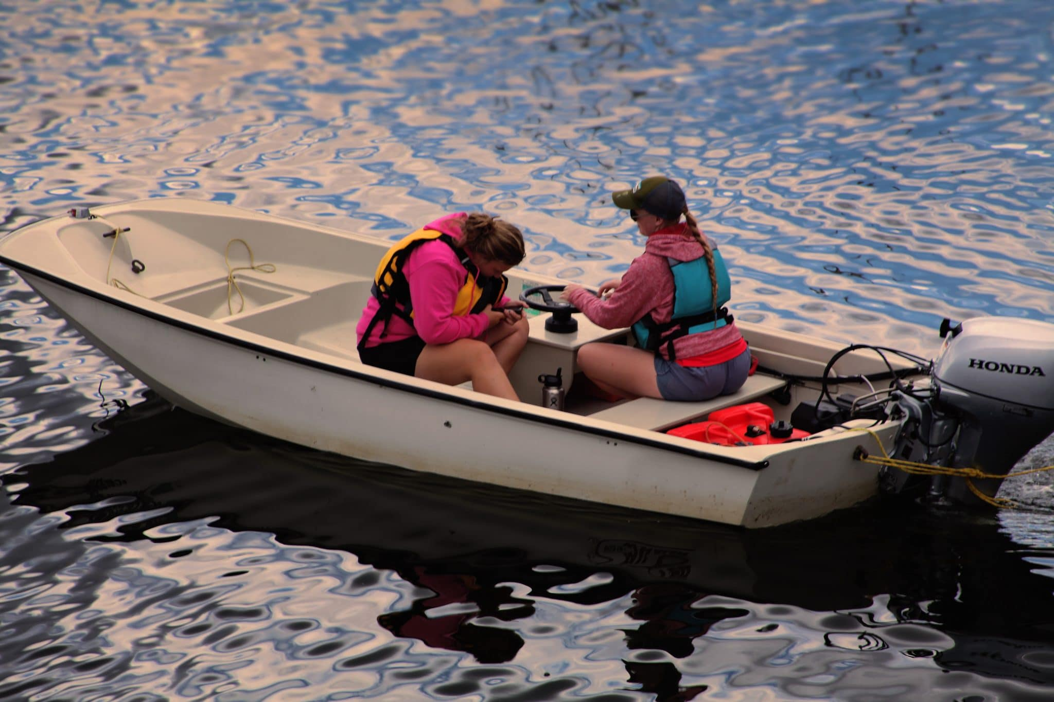 2 ladies in a bay boat on a body of water
