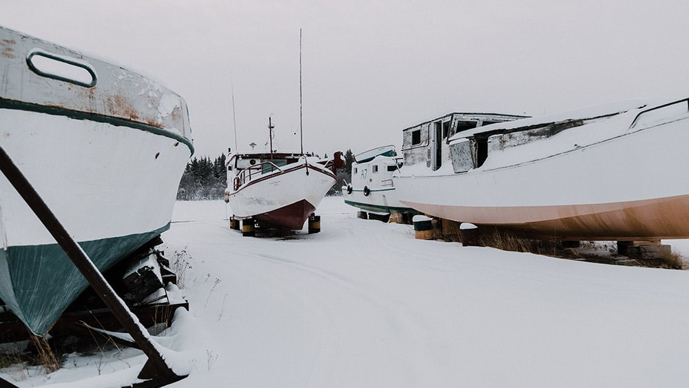 Boats moored on land covered in snow
