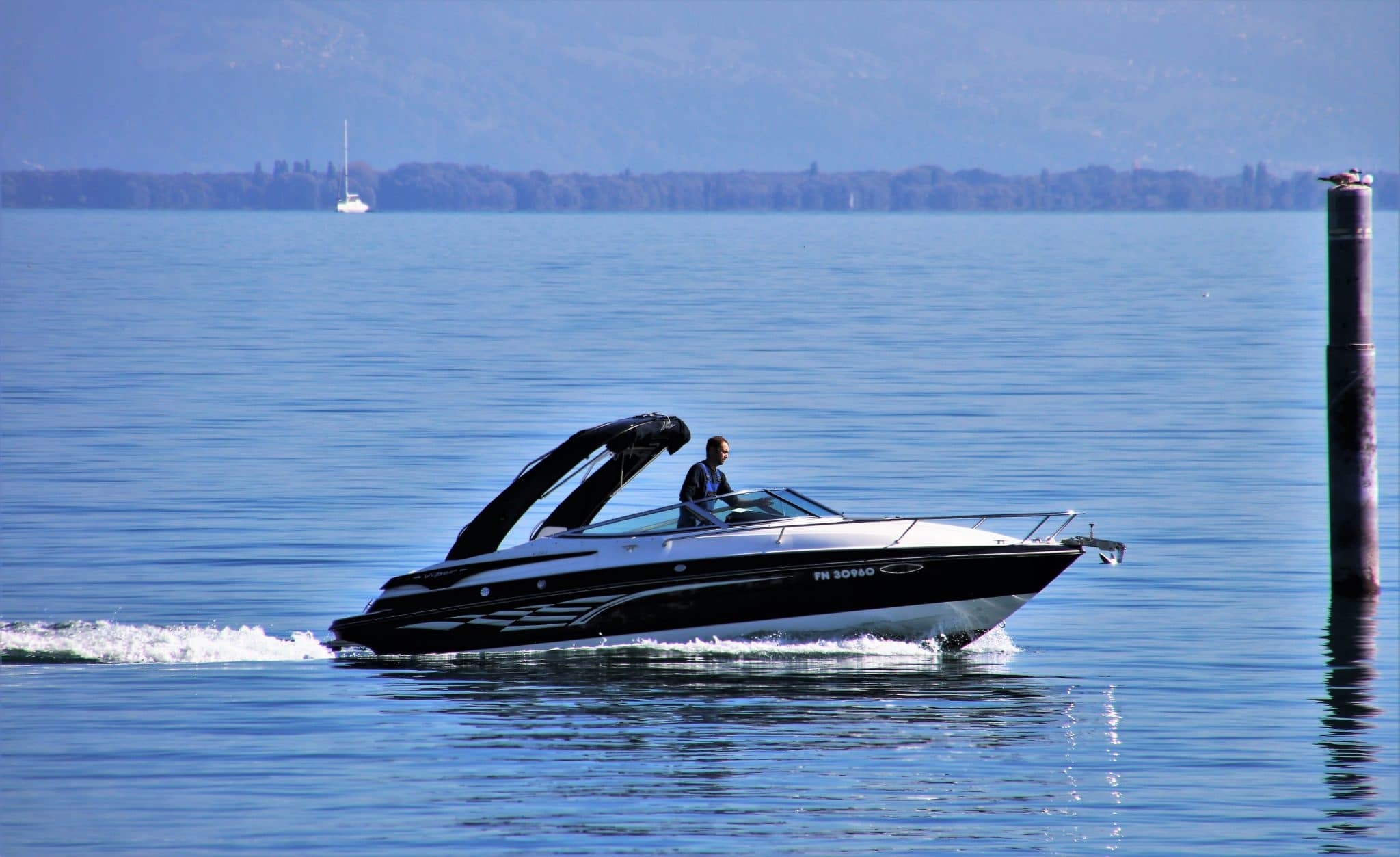man driving a jet boat on a body of water