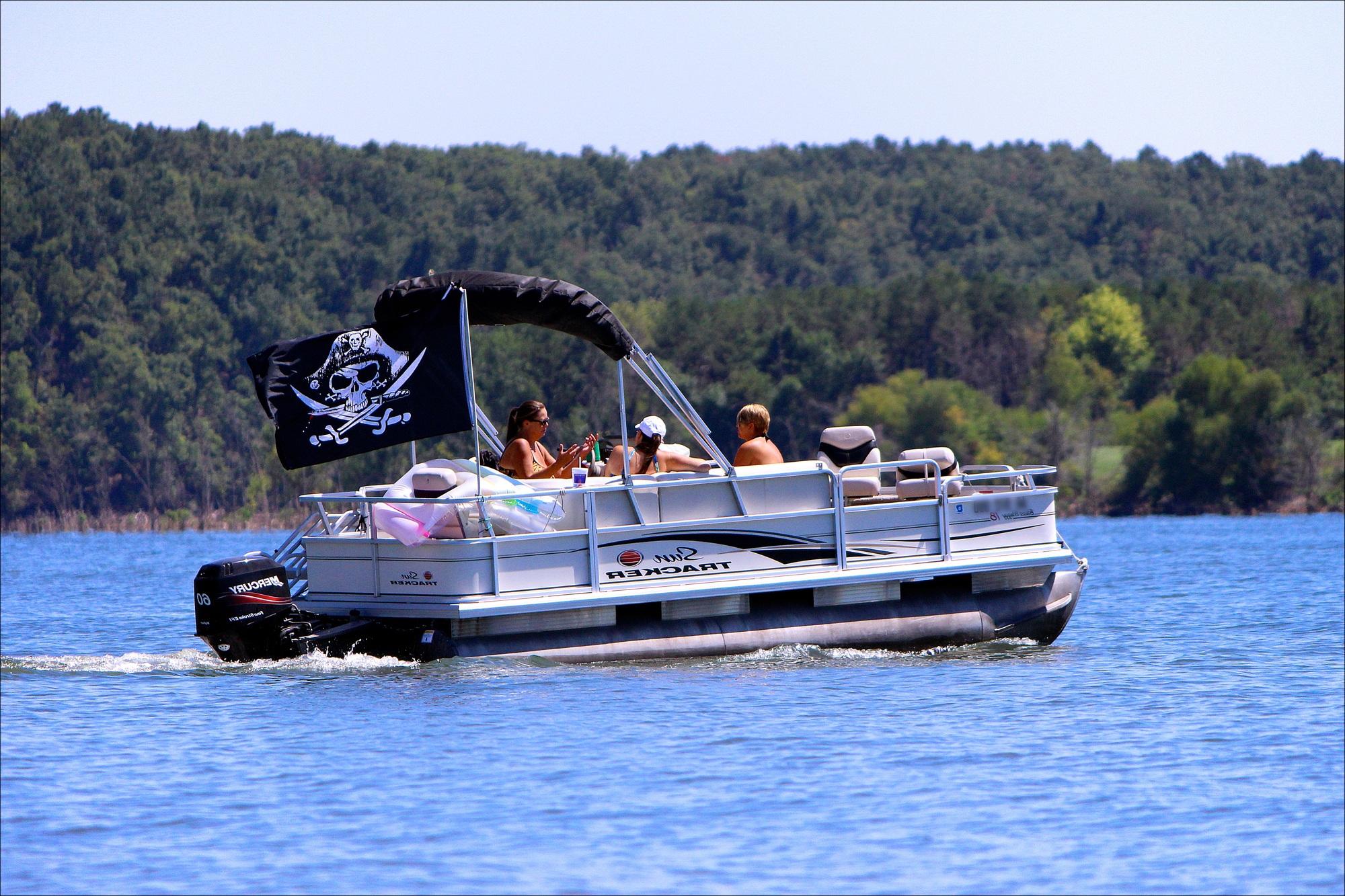3 people aboard a pontoon boat