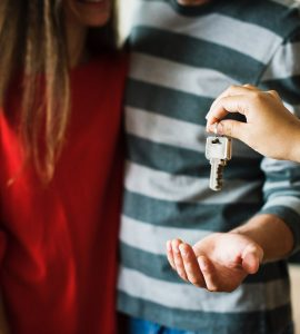 A couple being handed keys to their property
