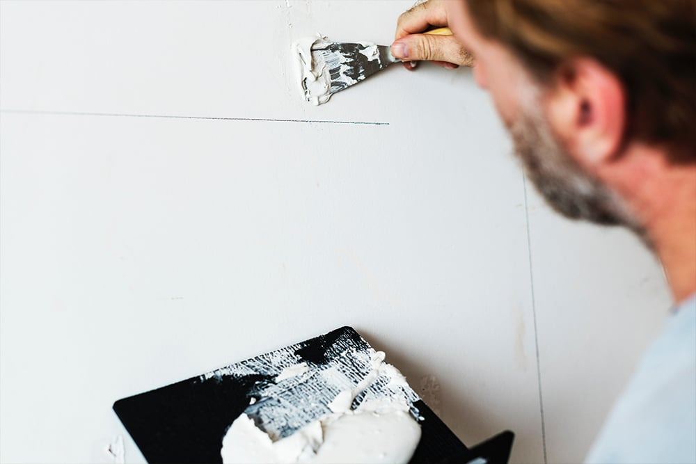 Man using filler on a wall