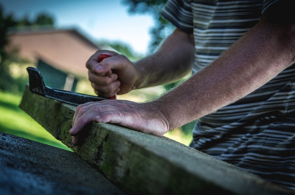 Man planing wood in a yard