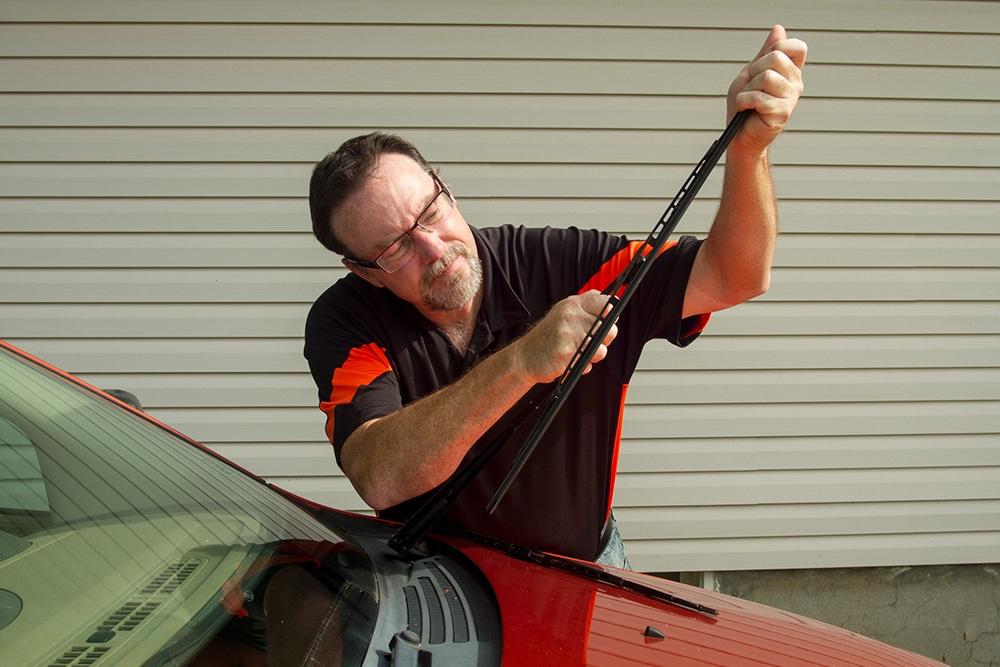 Man replacing windscreen wipers