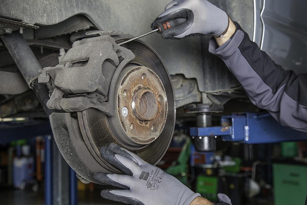Man replacing worn brake pads