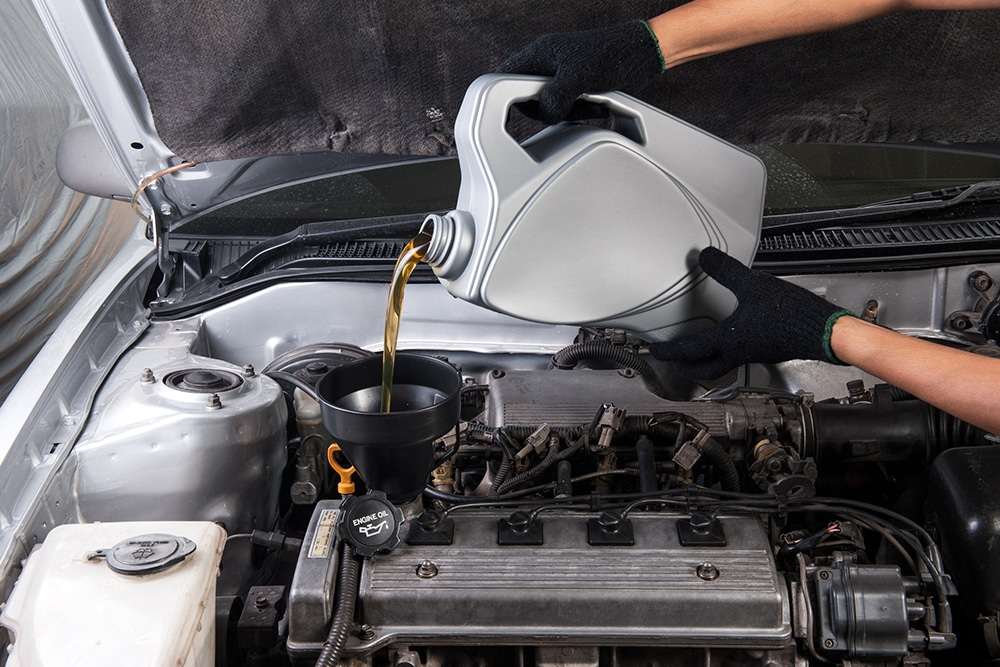Person filling their engine with oil
