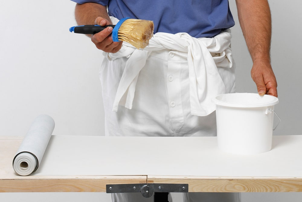 Man holding a wallpaper paste brush