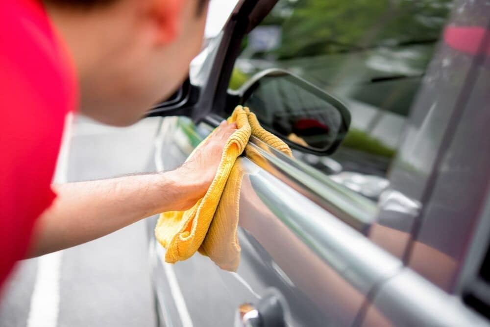 car being cleaned with a cloth