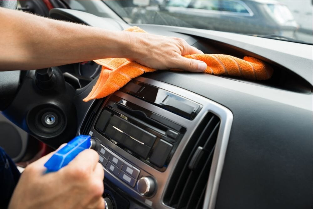 dashboard being cleaned with a cloth