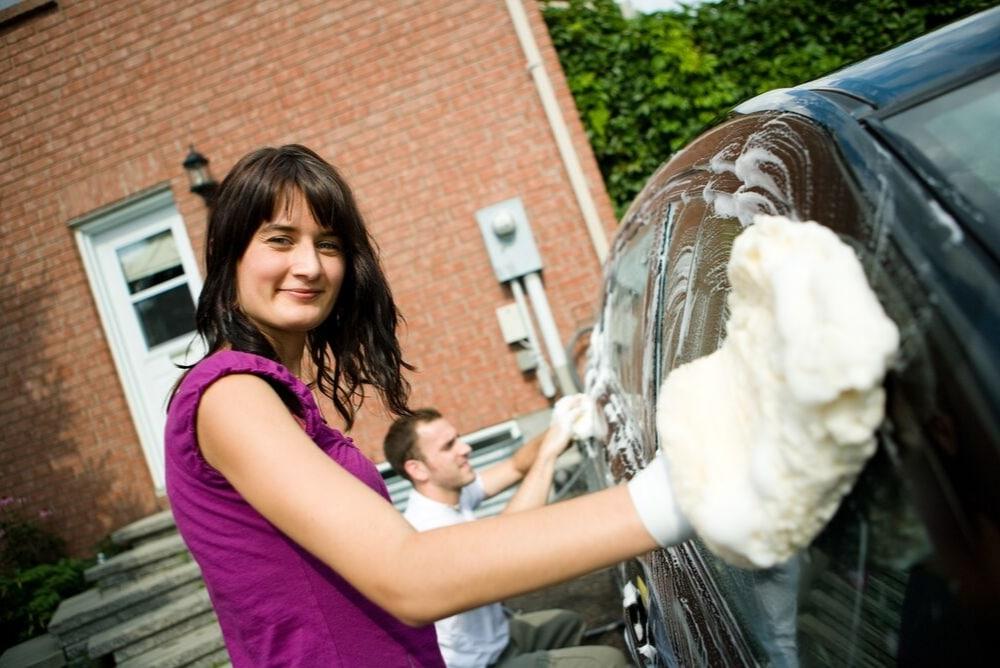 Lady washing a car with a mitt