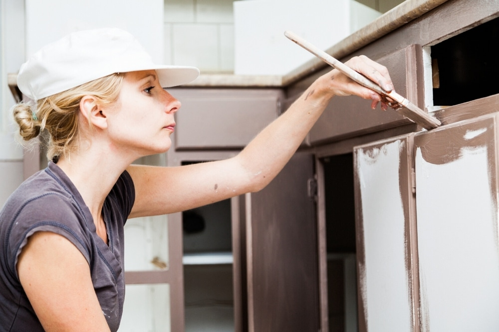 woman painting kitchen cupboards