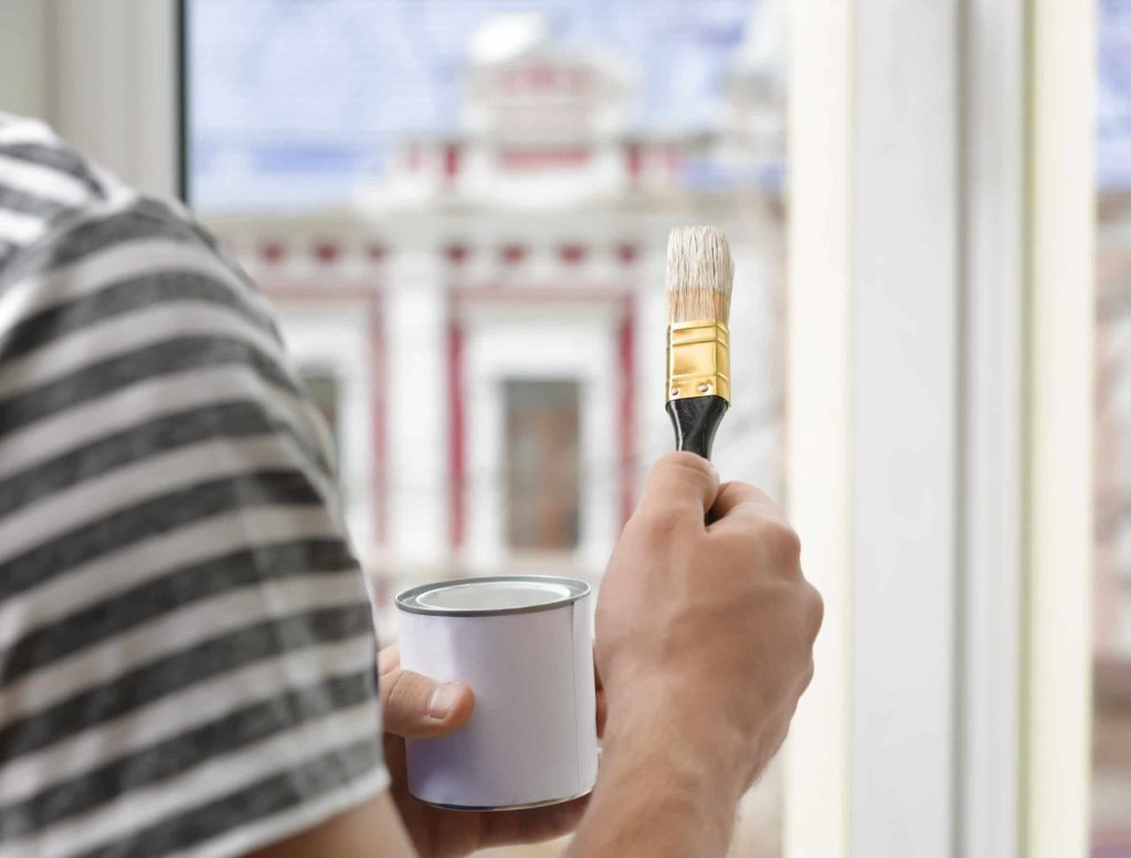 Man holding paint brush and tin of paint