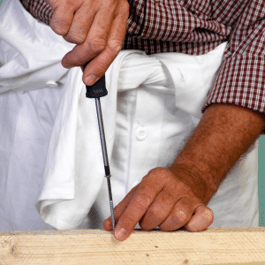 Man using a screw driver on a screw