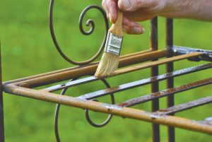 Owatrol Oil being applied to metal outdoor chair